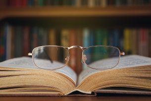 משקפים מעל לספר ברקע ספרייה