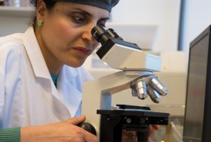 לבורנטית מעבדה מביטה במיקרוסקופ