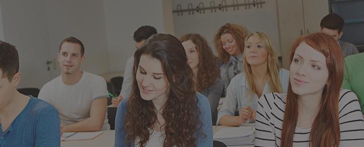 תלמידים יושבים בשולחנות בכיתת לימוד